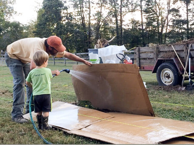 Watering down cardboard, a base layer of our sheet mulch bed.